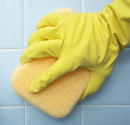Cleaning shower tile with a sponge and spray